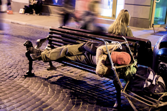 A homeless man sleeping on a bench at night in the city