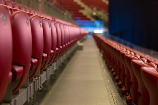 Rows of empty red concert chairs.